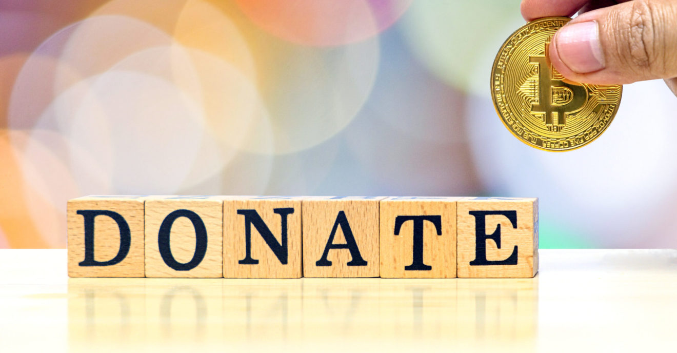 Donate concept idea, close-up hands of man who holding gold coin for give to donate wooden letters on bokeh blur background, informative and communication about donations money for assist and support